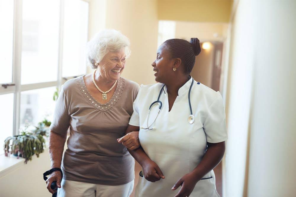 Caretaker walking with resident at Morningside Nursing and Rehabilitation Center.