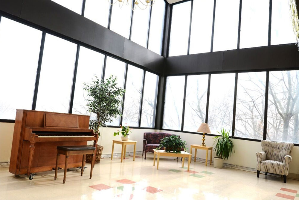 Lobby of Norwalk facility with open concept, tall ceilings, and piano.